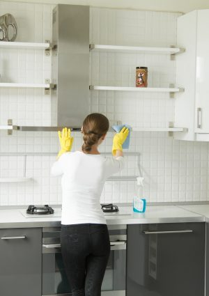 Rear view at a young woman washing shelves of kitchen closet. Kitchen cabinet in white and black colors, modern apartment interior in scandinavian style. Home, housekeeping concept